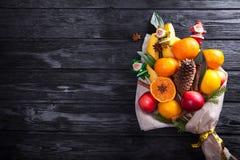 Zoet eetbaar die boeket van vruchten wordt gemaakt in document op zwarte achtergrond worden verpakt Stock Foto
