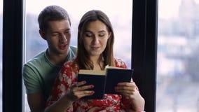 Zoet jong paar die een boek samen thuis lezen stock footage