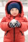 Zoet kind in de sneeuw met een sneeuwbal in zijn handen Royalty-vrije Stock Fotografie
