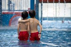 Zoet kind, jongen, die in de speelplaats van de waterwereld, spelen die genieten van bij Stock Foto