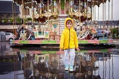 Zoet kind, jongen het letten op carrousel in de regen, die geel r dragen Royalty-vrije Stock Afbeeldingen