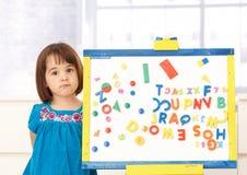 Zoet klein meisje dat zich bij tekenbord bevindt Stock Foto's