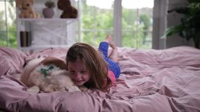 Zoet meisje die slaperig puppy in bed knuffelen stock video