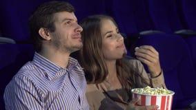 Zoet paar die op romantische komedie letten bij de bioskoop stock fotografie