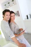 Zoet paar in keuken die tablet gebruiken Stock Afbeelding