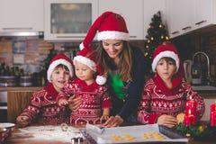 Zoet peuterkind en zijn oudere broer, jongens, die mama helpen die Kerstmiskoekjes thuis voorbereiden stock fotografie