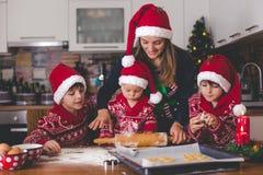 Zoet peuterkind en zijn oudere broer, jongens, die mama helpen die Kerstmiskoekjes thuis voorbereiden royalty-vrije stock foto