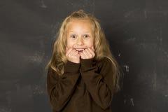 Zoet schoolmeisje in het eenvormige lachen opgewekt voor het bord van de schoolklasse gelukkig glimlachen Stock Foto's