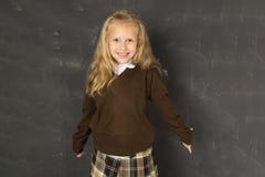 Zoet schoolmeisje in het eenvormige lachen opgewekt voor het bord van de schoolklasse gelukkig glimlachen Royalty-vrije Stock Afbeeldingen