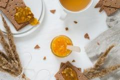 Zoet snack of ontbijt met Zweedse crackers van het rogge de kernachtige brood, uitgespreide oranje jam, kop met groene thee, jam  stock foto