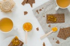 Zoet snack of ontbijt met Zweedse crackers van het rogge de kernachtige brood, uitgespreide oranje jam, koppen met groene thee Stock Afbeeldingen