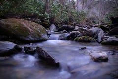 Zoet waterrivier met de Langzame Fotografie van de Blindsnelheid en Rotsen met Mos Stock Fotografie