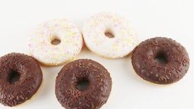 Zoet wit en chocolade donuts stock footage