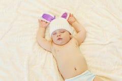 Zoete baby in gebreide hoed met een slaap van konijnoren op bed Stock Afbeelding