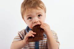 Zoete babyjongen die een chocoladereep eten Royalty-vrije Stock Foto's