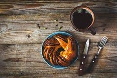Zoete broodje en kop van zwarte koffie op uitstekende houten lijst Stock Afbeeldingen