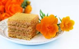 Zoete cake en bloemen dichtbij het Stock Fotografie