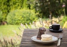 Zoete cakes op witte plaat met vork op rustiek bureau in garde Royalty-vrije Stock Fotografie