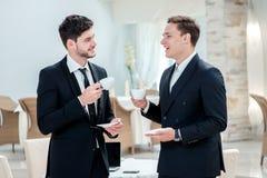Zoete croissant en een kop van koffie op de achtergrond Twee andere zakenman het drinken koffie en het spreken Royalty-vrije Stock Foto