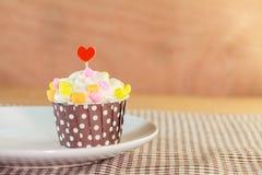Zoete cupcake op schijf met houten kleur als achtergrond stock foto's