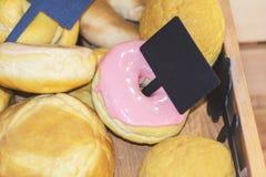 Zoete donuts die met roze in de doos met markering berijpen stock afbeeldingen