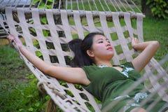 Zoete en ontspannen Aziatische Chinese vrouw die op haar jaren '20 het groene de Zomerkleding liggen nadenkende peinzend en comfo Royalty-vrije Stock Foto's