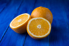 Zoete gehele sinaasappelen en de twee helften op een blauwe houten achtergrond Stock Afbeeldingen