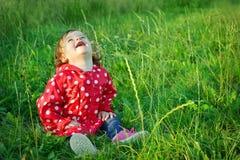 Zoete gelukkige meisjezitting in gras openlucht Leuke baby met het krullende haar laughting Het jonge meisje stellen in park Glim Royalty-vrije Stock Foto's