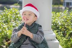 Zoete Gemengde Rasjongen die Santa Hat Eating Candy Cane dragen royalty-vrije stock afbeeldingen