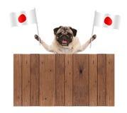 Zoete het glimlachen pug puppyhond met Japanse Nationale vlag en houten omheining Royalty-vrije Stock Foto's