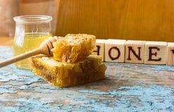 Zoete honing in de kam Op landelijke houten achtergrond Glasbank met honing Royalty-vrije Stock Afbeelding