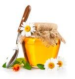 Zoete honing in glaskruik met lepel en bloemen royalty-vrije stock afbeeldingen