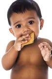 Zoete Indische baby die een koekje eet stock foto's