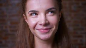 Zoete kalme artistiek en binnen glimlach erachter stellen die van Kaukasisch rood meisje, zich calmly, bakstenen muur bevinden stock videobeelden