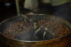 Zoete kastanjenoten die voor het eten in een het draaien trommel roosteren Royalty-vrije Stock Fotografie