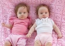 Zoete kleine tweelingen die op een roze deken liggen. Royalty-vrije Stock Afbeeldingen
