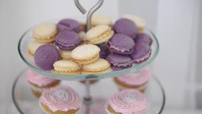 Zoete kleurrijke macarons klem Kleurrijke die Amandelkoekjes prachtig in een vaas voor snoepjes op witte achtergrond worden verfr stock footage
