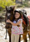 Zoete mooie jong meisje 7 of 8 jaar oud het koesteren hoofd van weinig poneypaard die de gelukkige dragende helm van de veilighei Stock Foto's