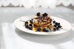 Zoete ontbijtpannekoeken met bosbessen en ahornstroop stock foto's