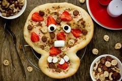 Zoete pizza in de vorm van grappige schedel om jonge geitjes in Hallowee te behandelen Stock Foto's