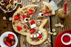 Zoete pizza in de vorm van grappige schedel om jonge geitjes voor Hallowe te behandelen Stock Foto's
