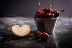 Zoete rijpe kersen in metaalemmer met stuk van appel op een lijst Gorisontalschot Stock Afbeelding