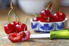Zoete rode kers met ceramisch mes op een oude houten lijst Stock Foto's
