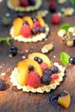 Zoete, rode, zwarte framboos en bes, perzik, honing op wafel op houten textuur dichte omhooggaand Stock Afbeeldingen