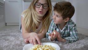 Zoete tand, kleine jongen met mum in glazen die koekjes van plaat eten die op vloer in ruimte liggen stock videobeelden