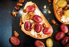Zoete toost met rode druif, ricotta, okkernoot bij het zwarte baksel Stock Fotografie