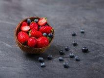 Zoete verse aardbeien en bosbessen in kom op een donkere achtergrond Het concept van het voedsel Stock Foto