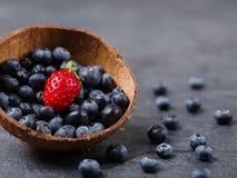 Zoete verse aardbeien en bosbessen in kom op een donkere achtergrond Het concept van het voedsel Royalty-vrije Stock Afbeeldingen