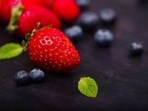 Zoete verse aardbeien en bosbessen op een donkere houten lijst Het concept van het voedsel Stock Afbeelding