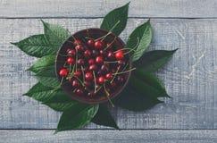 Zoete verse kersen met groene bladeren op blauw rustiek hout Stock Afbeelding